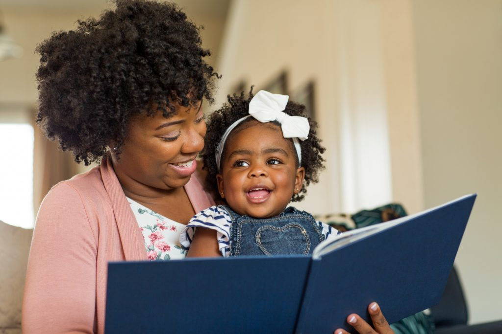Image of black woman reading to a very happy child.