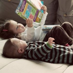 Image of two small children laying on their backs reading a book.