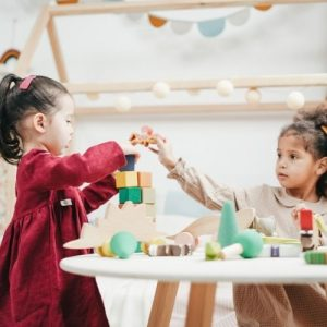 Image description: a child in a red dress plays with blocks at a table while another child with long wavy hair helps out