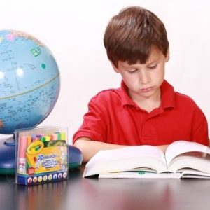 Image description: young child with brown hair and red polo sits next to a globe and a box of markers while studying a book. This is the most stock photo-y of stock photos ever.