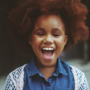 Image description: young black child with open mouth smile wearing a blue polo shirt