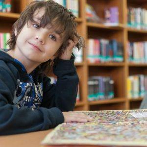 Image description: kid wearing black hoodie sits in library next to finished puzzle