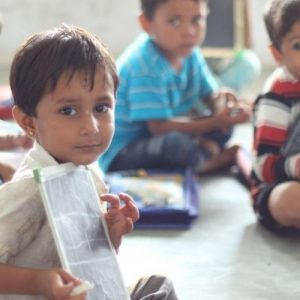 Image description: young child holds up a white board while two other children sit behind him looking on.
