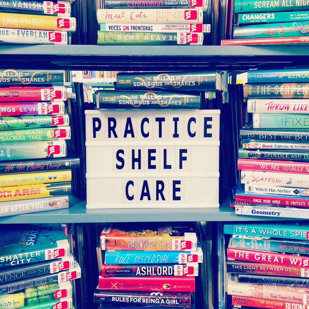 """Piles of books surrounding a sign that reads """"Practice Shelf Care"""""""