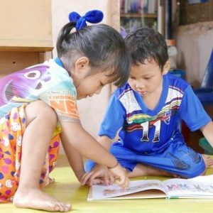 Image description: two young children in brightly colored clothing sit on the floor and share one book