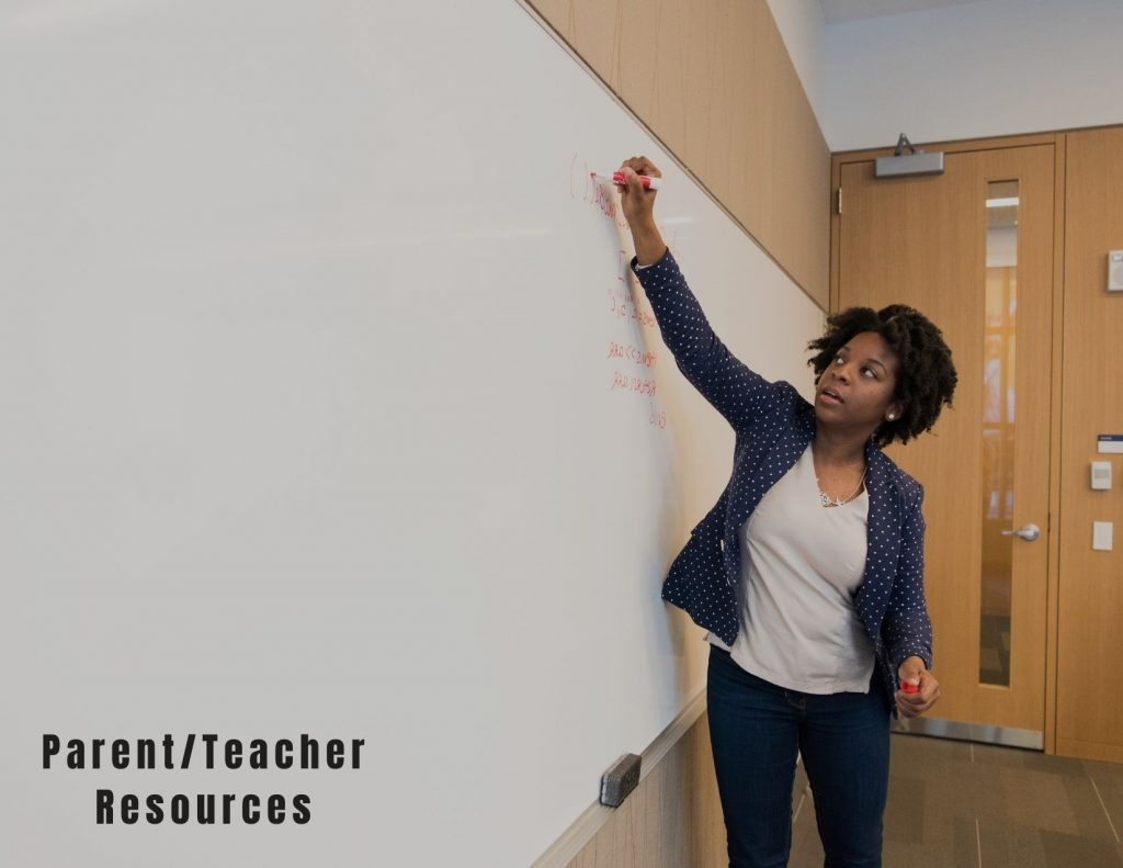 Image Description: a black person wearing a white v neck tee shirt and professional jacket writes with an orange marker on a giant white board. In the lower left corner bold text reads 'parent/teacher resources'