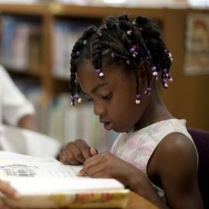 Image description: black child with braids sits at a table intently studying a book