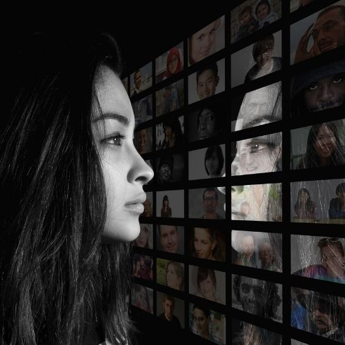 Image of a woman looking at a wall of screens with different images on it