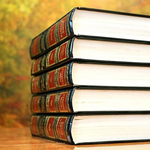 This is an image of a stack of large books stacked with spines out on a wooden table