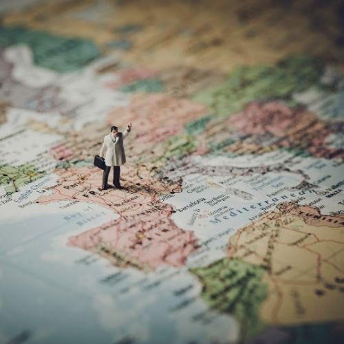 Image of a small toy person in a coat walking on a map of france