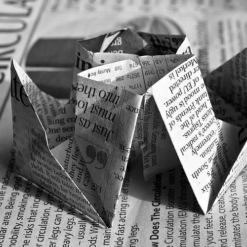 Image of a newspaper folded up like an origami game.