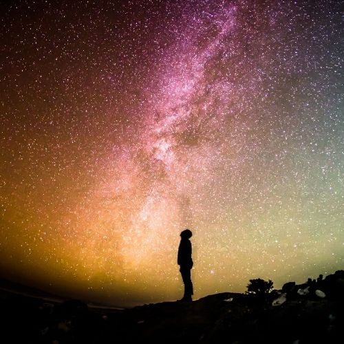 Image of the shilouette of a person starring up at the night sky full of stars