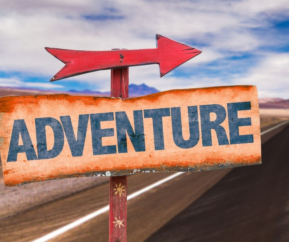 Image of a sign with a big red arrow pointing towards an open paved road with a blue sky spotted by white clouds in the background. sign reads 'adventure'