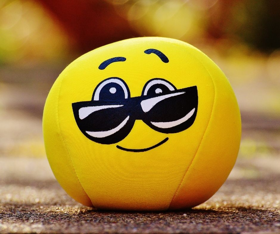 image of a yellow emoji ball with a smile and sunglasses and slightly arched eyebrows
