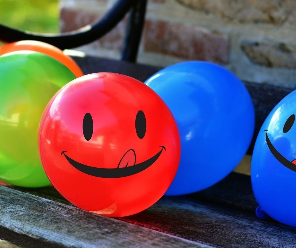Image of red, green, and blue balloons with smiley faces with tongues drawn on them. the balloons rest on a wooden bench