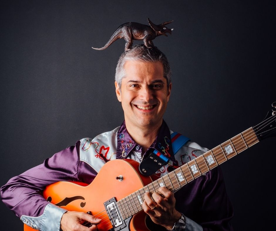 Image of Matt Heaton - a white man - holding a guitar with a toy triceratops on his head