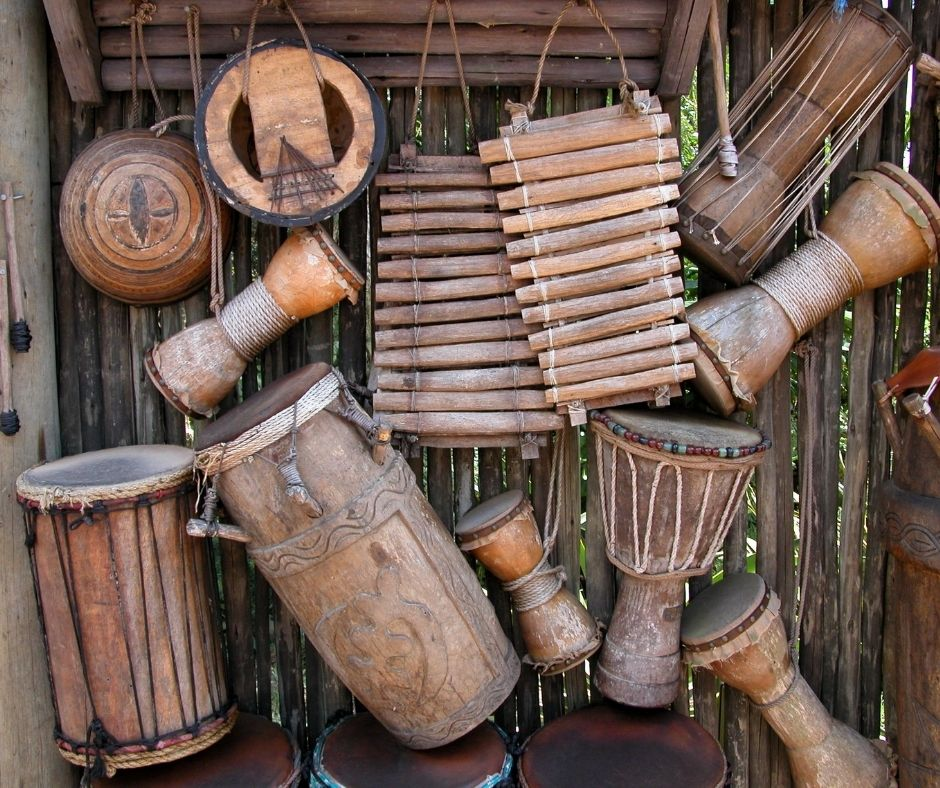 Image description of a rustic wooden wall with several wooden drums and two wooden xylophones hanging from it.