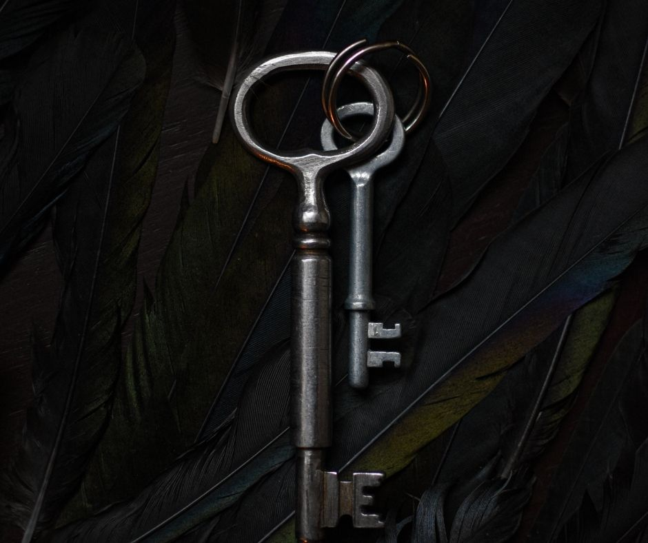 Image of two skeleton keys on a background of raven wings