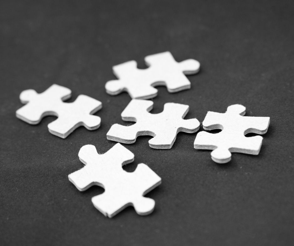 Image of five white puzzle pieces on a gray counter