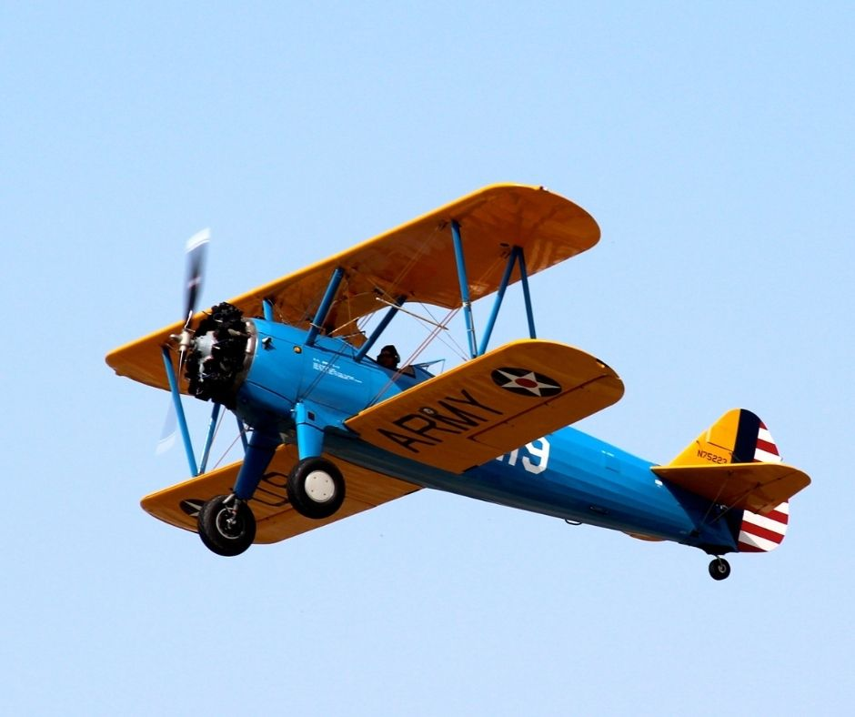 image of an old blue and orange army bi-plane flying in a blue sky
