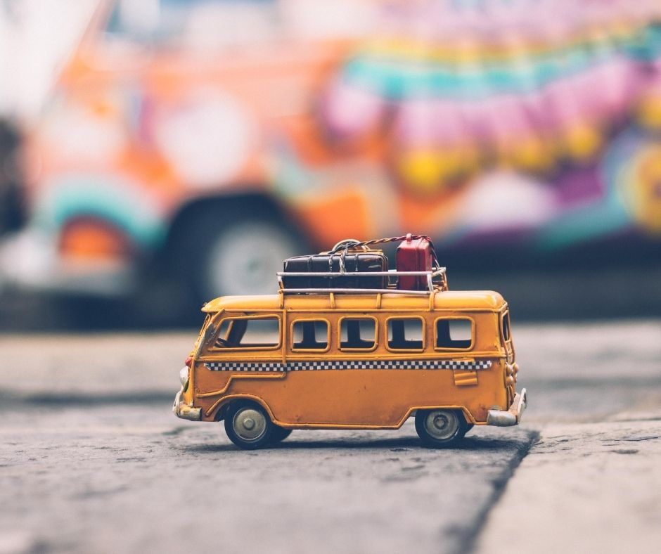 Image of a toy yellow bus/van with luggage on the roof