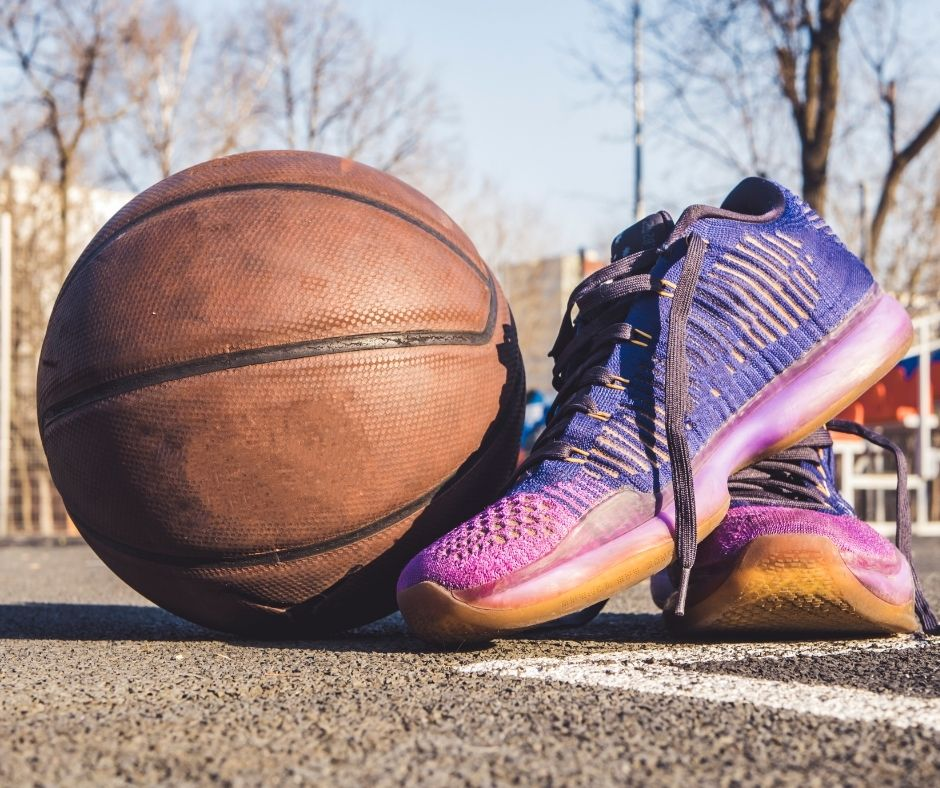 Image of an old basketball next to purple and pink sneakers