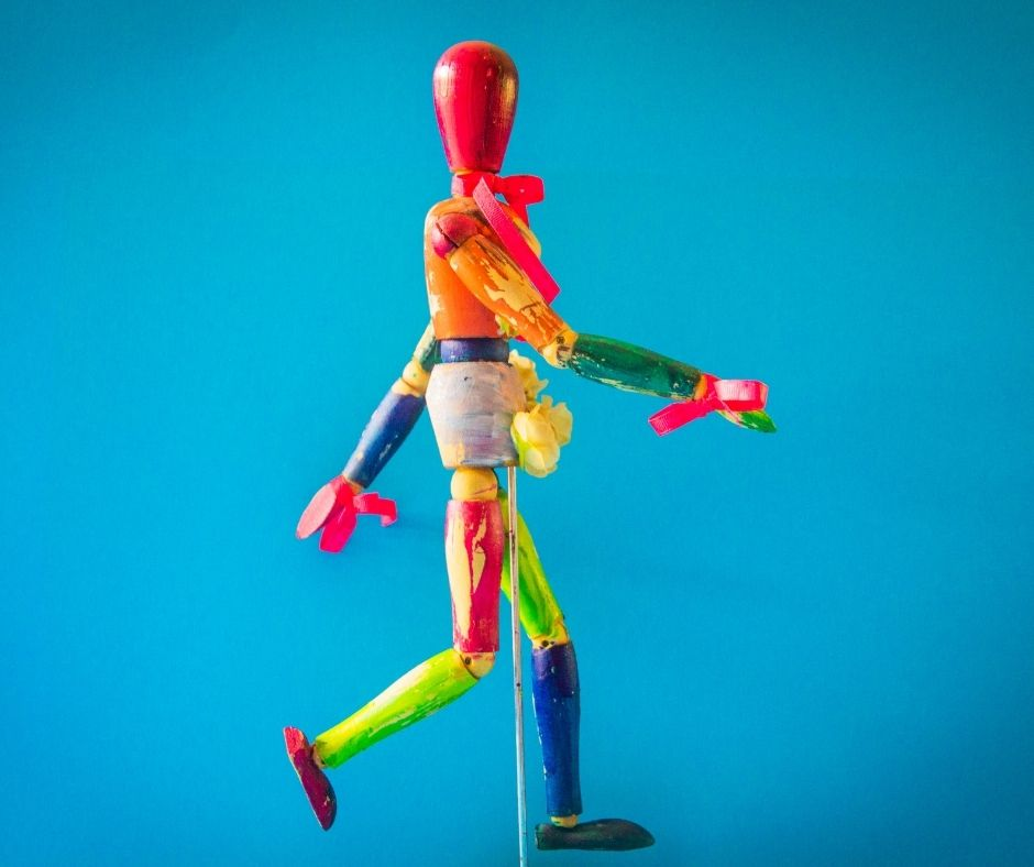 Image description is of a wooden model doll painted vibrantly. Backgraound is blue.