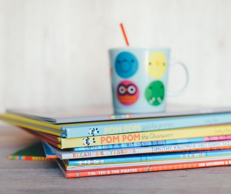 Image description: a stack of colorful children's books are stacked spine out with a brightly colored coffee mug resting on top