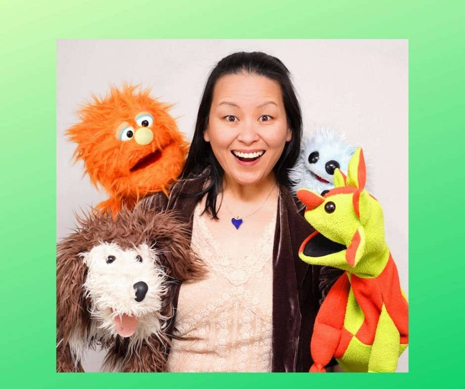 Image of a woman with a wide open mouth smile surrounded by puppets
